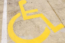 yellow wheelchair handicap road sign painted on a yellow pavement